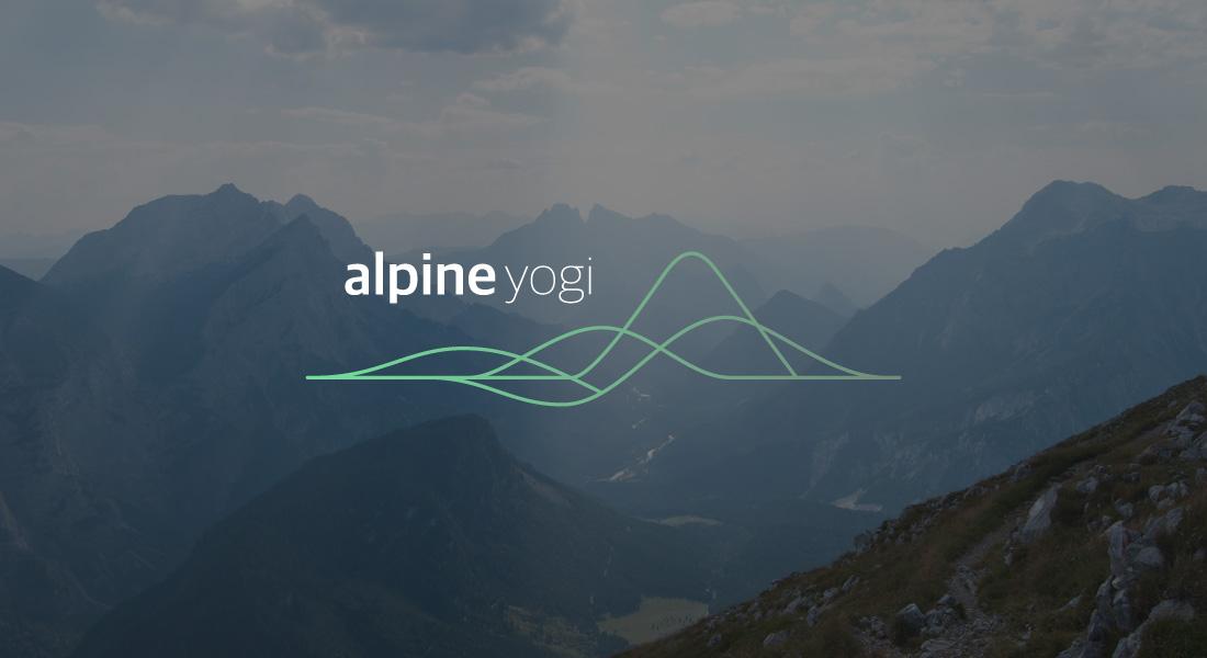 Adventure Yogi Alpine Logo with a mountainous view in the background